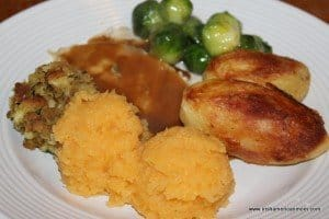 Turkey, stuffing or dressing, roast potatoes , rutabaga and brussels sprouts on a white plate