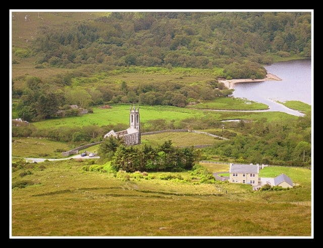 Looking down from a mountain on a valley with a house and church and a lake