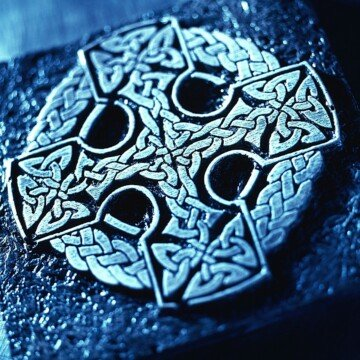 A round cross symbol with intricate Celtic knotwork