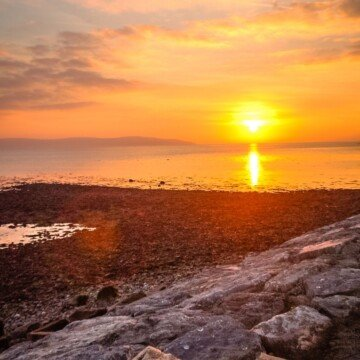 The sun setting over a body of water by a rocky shoreline