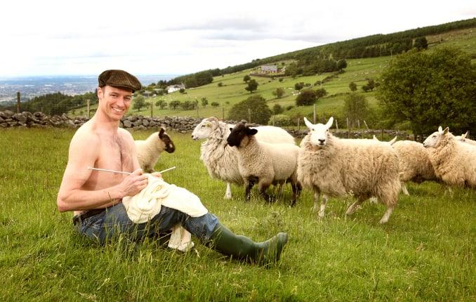 an Irish farmer in a field of sheep knitting an Aran sweater