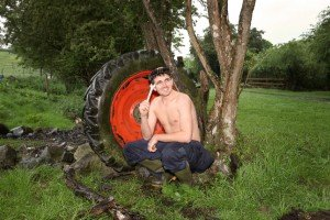 A farmer holds a spanner beside a tractor wheel in a field
