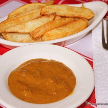 Dish of french fries beside a bowl of curry sauce