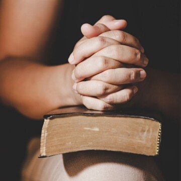 Hands held in prayer over a Bible balanced on a person's knee