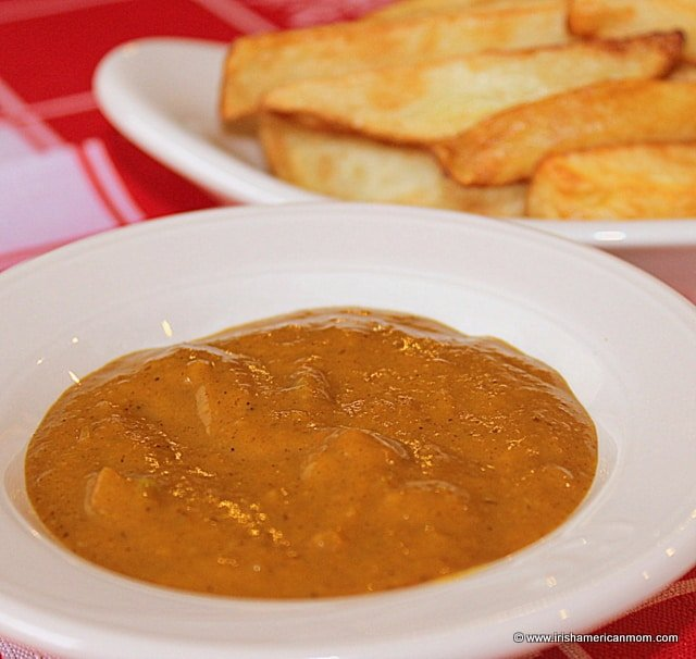 A side dish of curry sauce with Irish chips or French fries