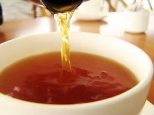 Tea being poured into a white cup