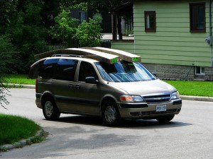Planks of wood balanced on top of a minivan