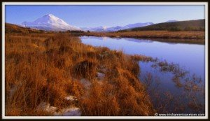 A winter lake beside a snow topped Mount Errigal in Ireland