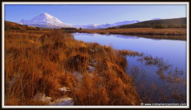 A winter lake beside a snow topped mountain