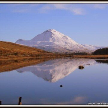 Blue sky and snow covered mountain reflecting in a Donegal lake