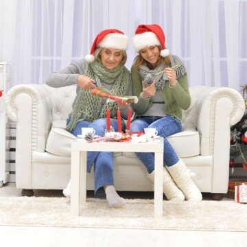 Two women in Santa hats sitting on a white sofa while lighting candles on a small table