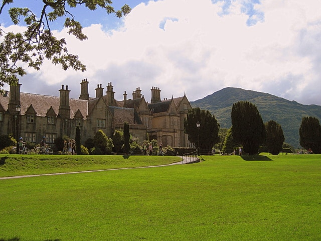 An old manor house in Ireland with multiple chimneys located beside a mountain and with lush green grass in front of it