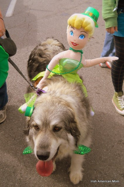 A dog with a doll dressed in green on its back