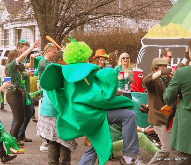 A group of people standing in a crowd while wearing green costumes