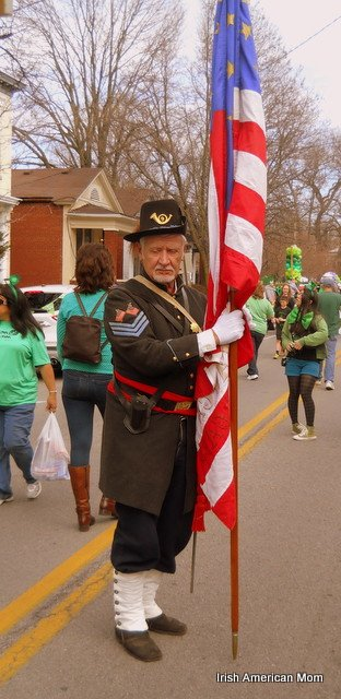 A man in vintage military uniform holding an American flag