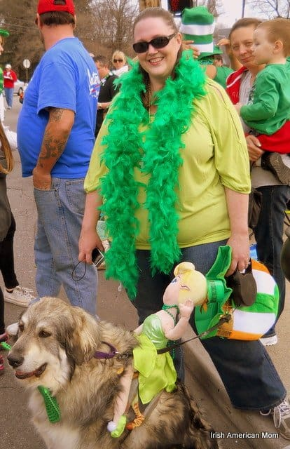 A woman wearing a green feather boa standing next to a dog