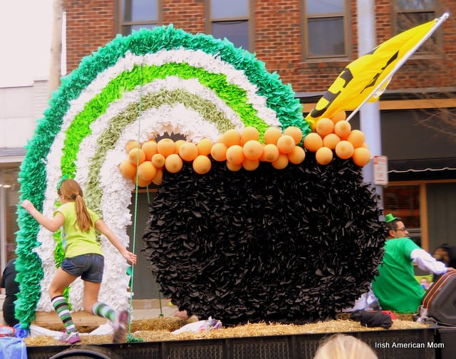 A pot f gold and green and white rainbow on a parade float