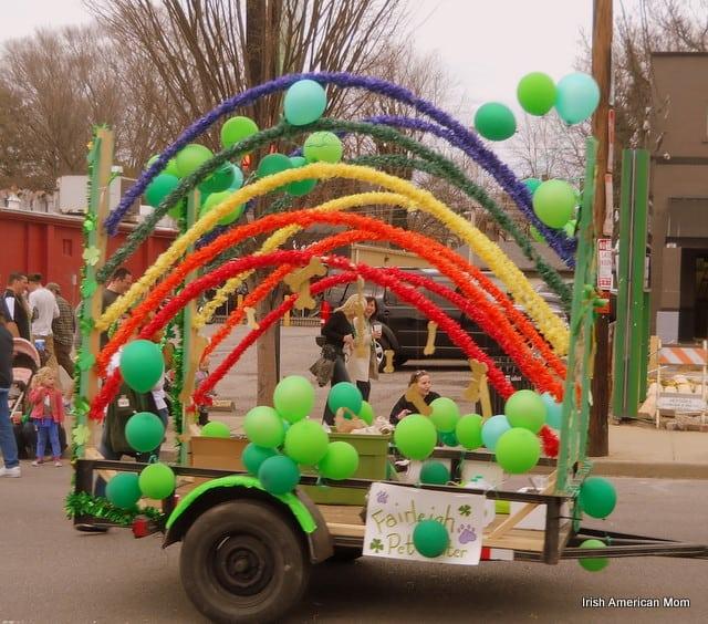 A rainbow and green balloon parade float