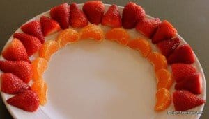 Red and orange arches of fruit to start a fruit rainbow on a platter