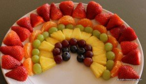 A layered colorful fruit rainbow on a plate
