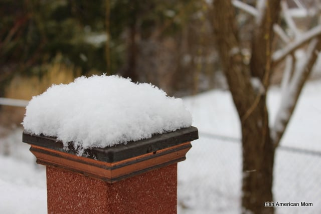 A pillar on a deck topped with snow