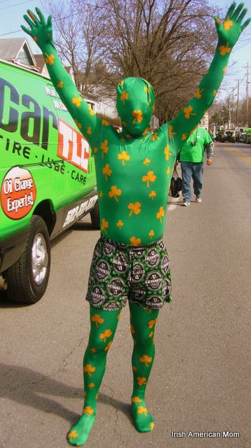 A man in a green and gold shamrock body suit with shorts