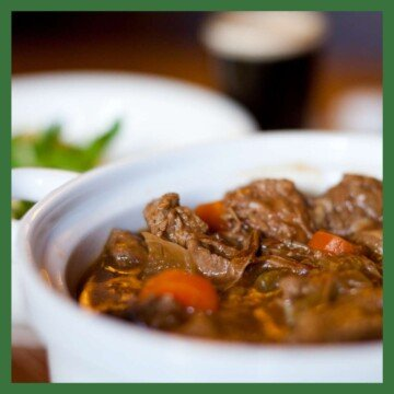 Bowl of stew with a glass of guinness in the background