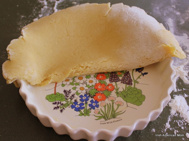 Laying a layer of pastry over a pie dish for almond berry tart crust