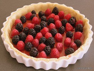 Putting a layer of red and black berries in a pastry shell for a custard fruit tart