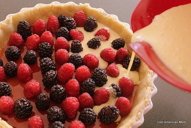 Pouring custard mix over berries for tart
