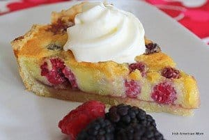 Cream swirled on top of a berry almond custart tart slice