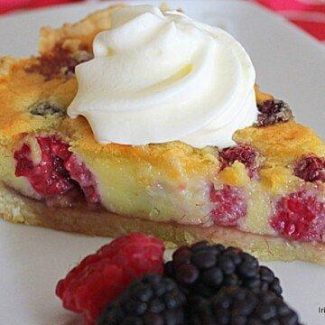Cream swirled on top of a berry almond custart tart slice