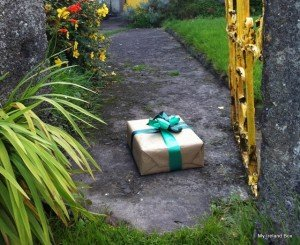 A green ribbon around a brown paper covered gift box from Ireland