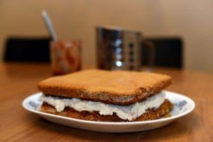A sponge cake with jam and cream on a plate