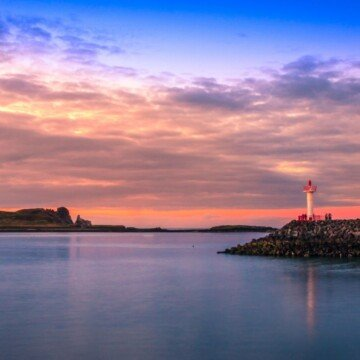 Sunset over water by a lighthouse beacon