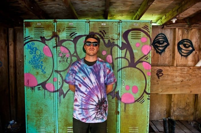 A man in a tiedye shirt poses beside graffiti on a wall of lockers