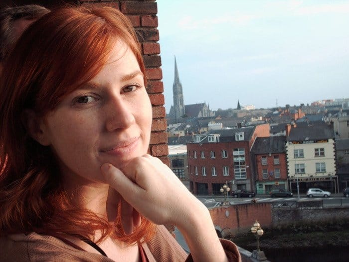 A red haired girl photographed on a balcony looking over city buildings