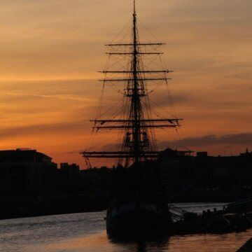 A wooden sail ship on a river at twilight