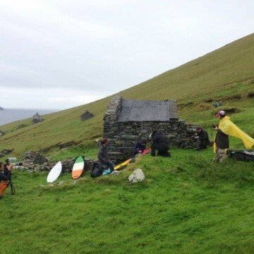 Irish flag surf board beside an abandoned house on the Blasket Islands