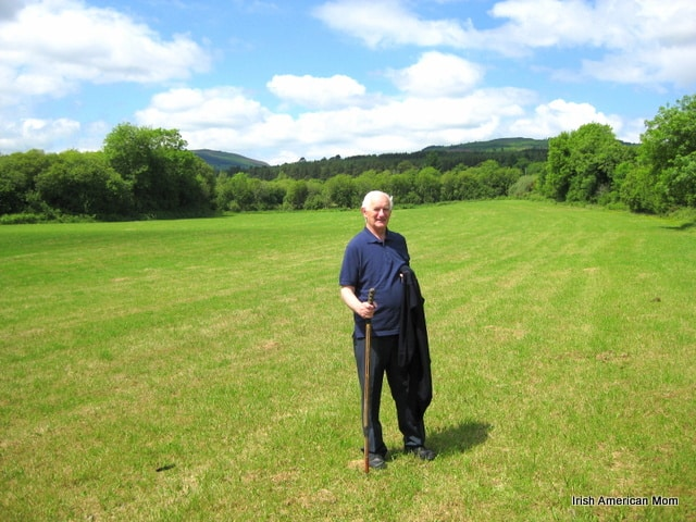 An Irish man with a walking stick in a green Irish field
