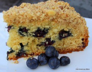 slice of lemon blueberry crumb cake with blueberries on a white plate