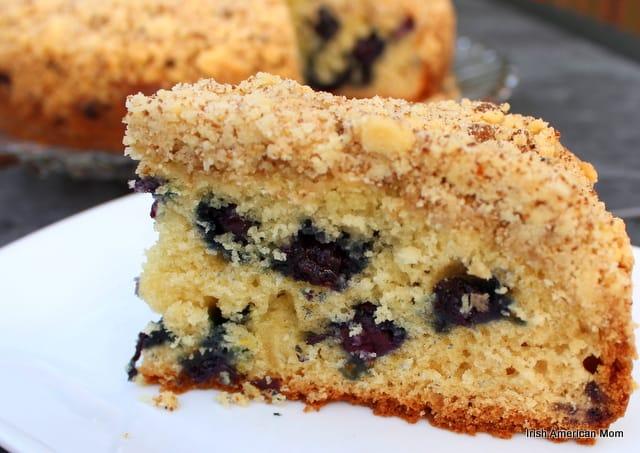 Blueberries spotting a slice of lemon blueberry crumb cake