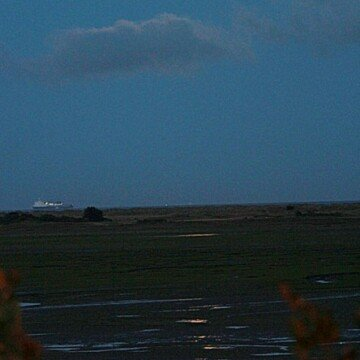 Reflection of the full moon on the sandy inlet by the Bull Island near Raheny Dublin