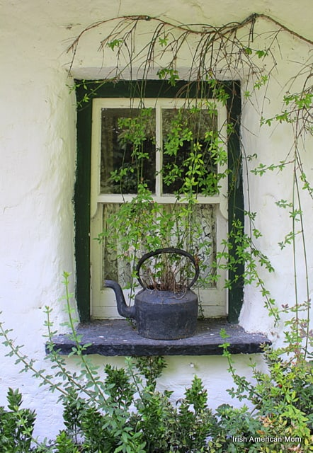 Green foliage around a thatched cottage window with a black kettle