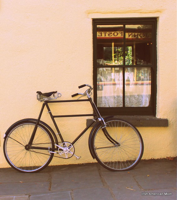 A bicycle parked on the side of a building and a window