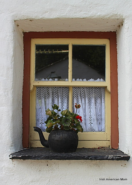 Black kettle flower display in an Irish cottage window sill