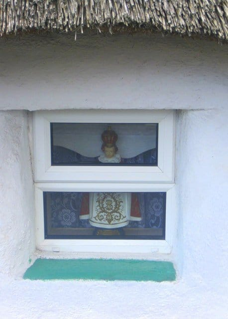 an Infant of Prague Statue inside an Irish cottage window