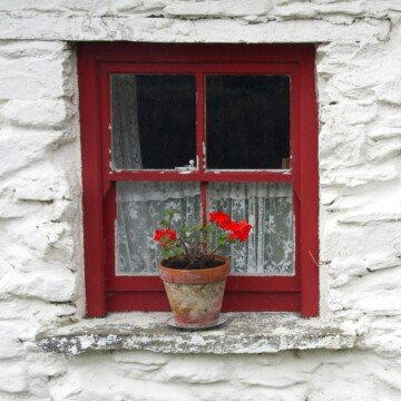 Red frame on a small window with a flower pot on the sill