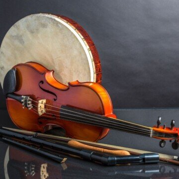 A hand drum, a fiddle and wind instruments displayed on a black surface