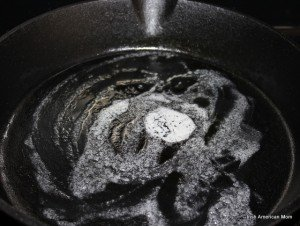 melting butter in a cast iron skillet for pumpkin pancakes